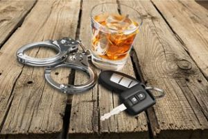 Alcohol with car keys and handcuffs.
